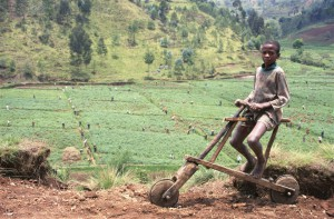 A young boy with his handmade wooden scooter stands on a hill overlooking farmers planting potatoes, Rwanda (IRIN)