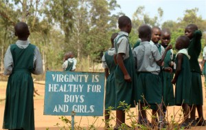 Children standing next to a sign that promotes abstinence, Uganda (IRIN) (2)